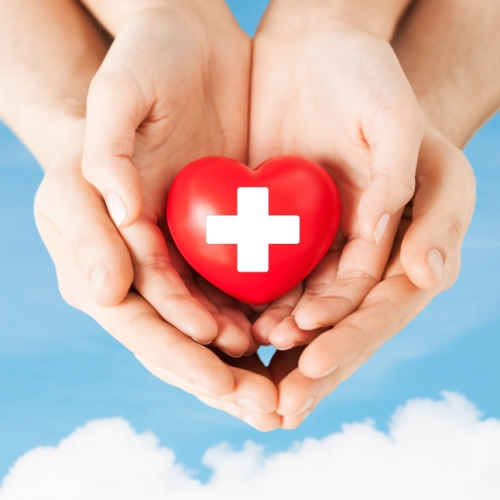 Male and female hands with a red first aid heart