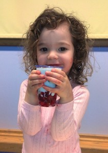 Smiling young girl with fruit yoghurt pot