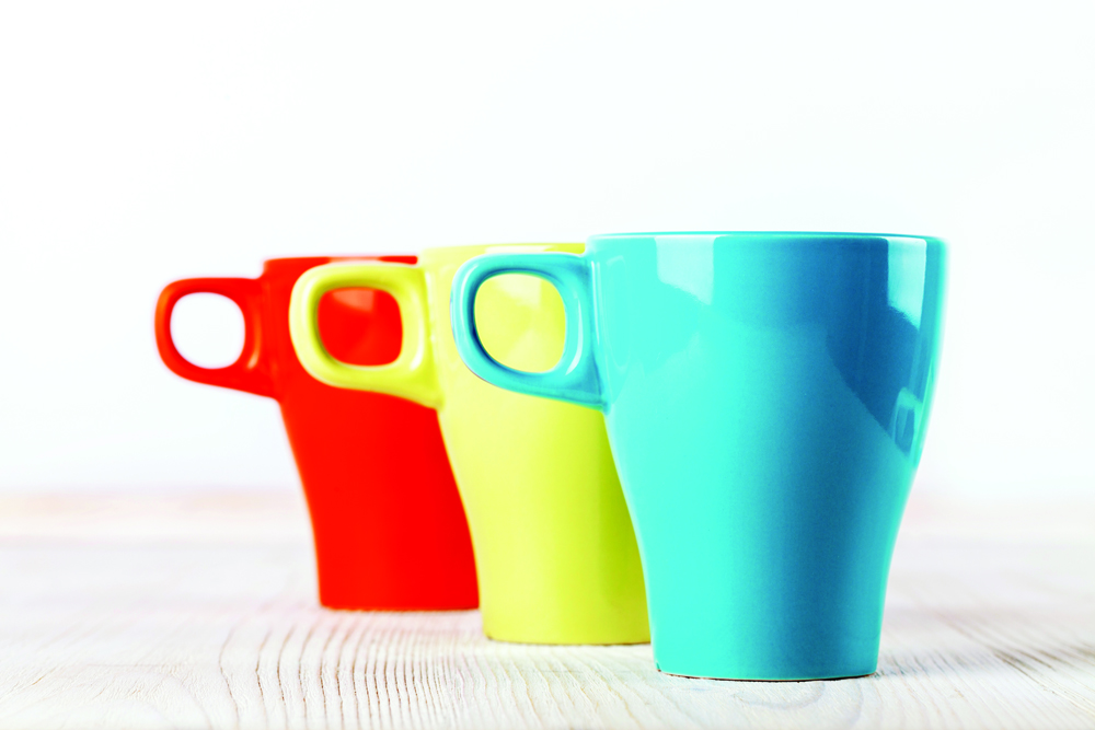 row of different colored china mugs